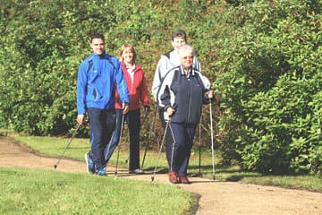 Reha-Patienten laufen Nordic Walking